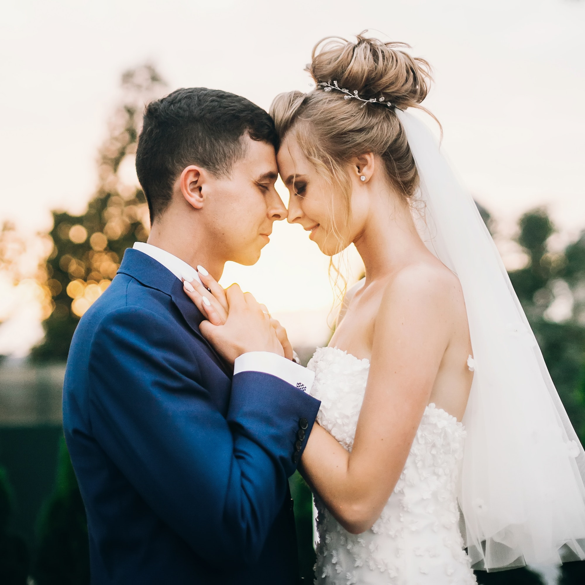 Stylish happy bride and groom posing in warm sunset light at wedding reception